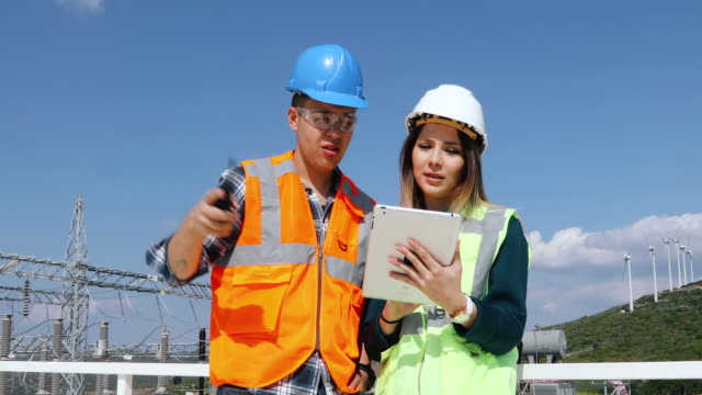 Young workers looking and checking wind turbines at field