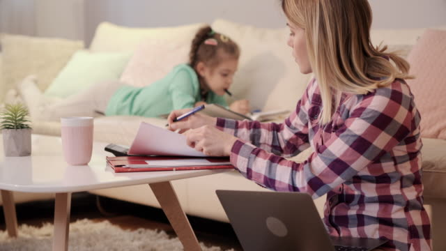 young working mother taking notes while using laptop and answering the phone call. - one parent stock videos & royalty-free footage