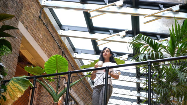 young working woman standing on balcony with cup of coffee - three quarter length stock videos & royalty-free footage
