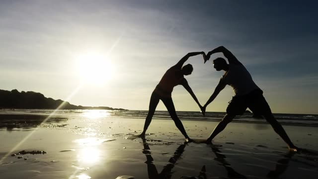 Young yoga couple move to create a heart on the beach