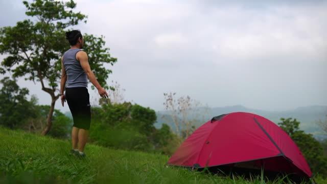 giovane yogi che fa esercizi sullo sfondo del fiume e della foresta. posa guerriera. vicino alla tenda in un'escursione - posa del loto video stock e b–roll