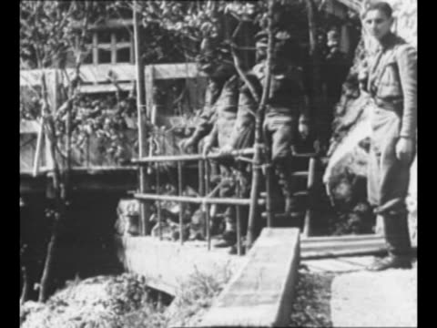 stockvideo's en b-roll-footage met young yugoslav partisan guard stands in foreground as he guards marshal josip tito's mountain headquarters in background / tito walks down steps of... - joegoslavië