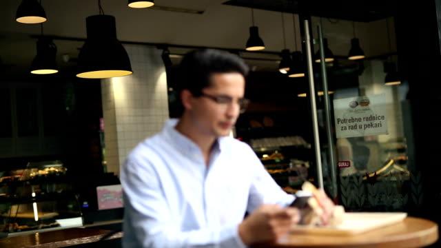 vidéos et rushes de homme d'affaires de jeune yuppie hipster dans café - sandwich