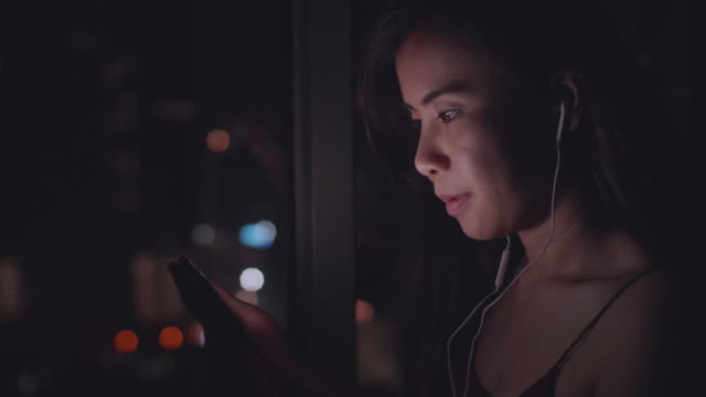 youngasian woman  listening to music on phone at night - video stock videos & royalty-free footage