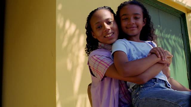 PORTRAIT younger Black girl sitting on Black teen girl's lap outdoors / hug + smile