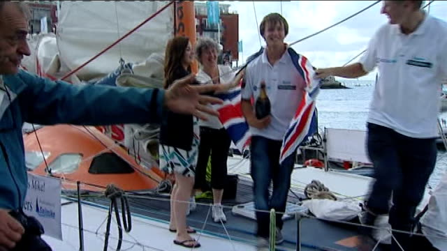 youngest roundtheworld yachtsman returns to portsmouth wellwishers in dinghy applauding press gathered around yacht at quayside mike wrapped in union... - cheek to cheek stock videos & royalty-free footage