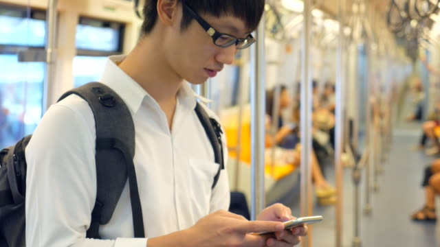 Youngman using smart phone on a train