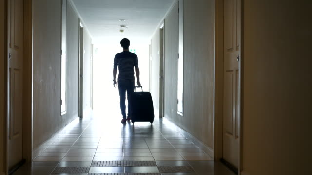 youngman with travel luggage walking to hotel room - wheeled luggage stock videos and b-roll footage