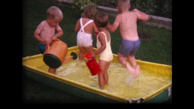 1962 youngsters in yellow backyard wading pool - watering can stock videos & royalty-free footage