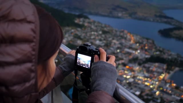 youngtraveller take a photo of city at dusk - queenstown stock videos & royalty-free footage
