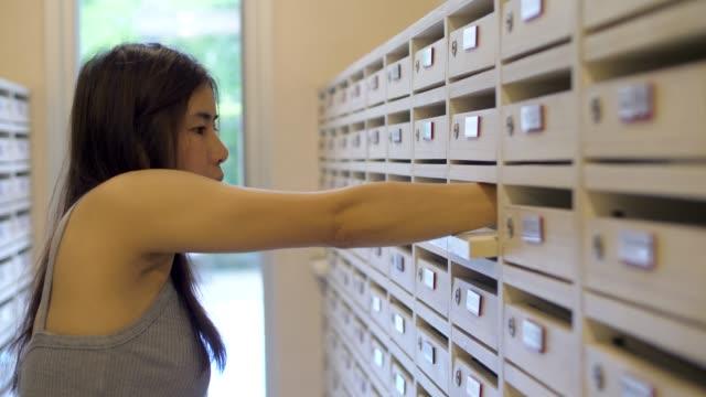 stockvideo's en b-roll-footage met youngwoman controle een postvak openen - brievenbus huis