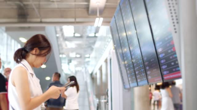 youngwoman 空港の飛行時間を検索 - 標識点の映像素材/bロール