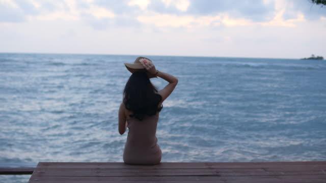 vídeos y material grabado en eventos de stock de youngwoman relajarse en la cubierta del océano - manos detrás de la cabeza