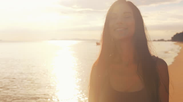 youngwoman walking along the beach at sunset - unrecognisable person stock videos & royalty-free footage