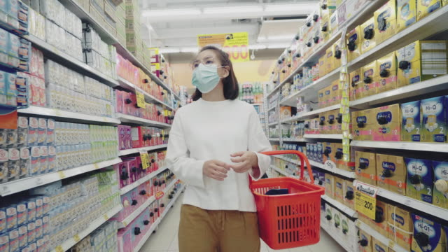 youngwoman wearing mask in supermaket for dried food - convenience stock videos & royalty-free footage
