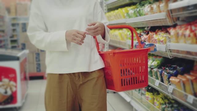vídeos y material grabado en eventos de stock de joven usando máscara en supermaket para comida seca - estante muebles