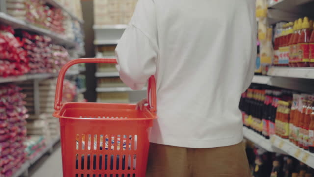 vidéos et rushes de jeune femme utilisant le masque dans le supermaket pour la nourriture sèche - panier courses