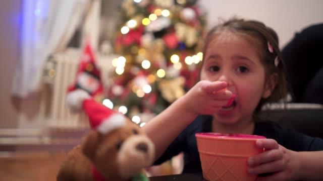 vídeos y material grabado en eventos de stock de el año viejo comiendo helado junto a un árbol de navidad - cuchara
