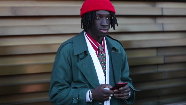 youssou bamar gueye seen wearing red beanie, green trench coat, white suit at fortezza da basso on january 8, 2020 in florence, italy. - トレンチコート点の映像素材/bロール