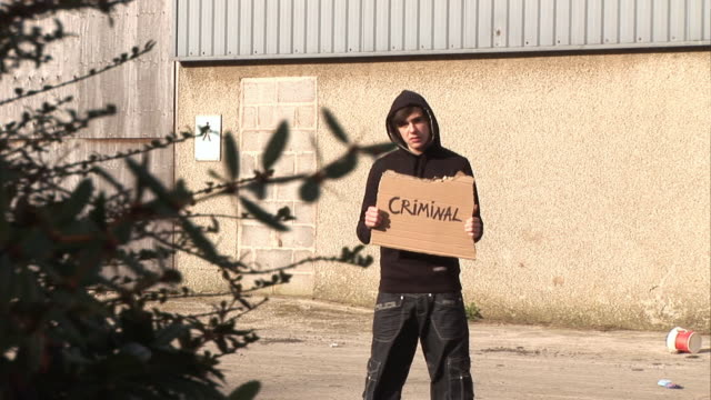"""youth / hoody holding sign saying """"criminal"""" - hood clothing stock videos and b-roll footage"""