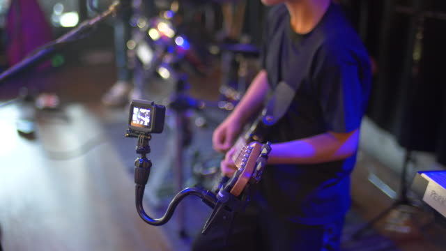 a youth musician guitarist rock star playing a guitar in a rock band on stage with an action camera gopro mounted. - klassischer rock and roll stock-videos und b-roll-filmmaterial