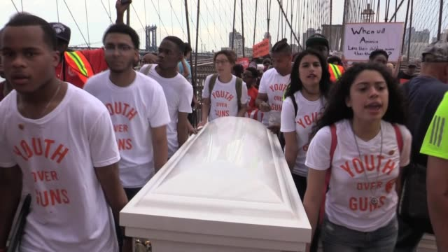 youth over guns moms demand action and thousands of students and parents march over brooklyn bridge carrying coffin to protest gun violence and... - controllo delle armi da fuoco video stock e b–roll
