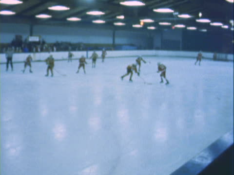 MONTAGE Youth playing ice hockey game, passing, falling and scrambling / California, United States