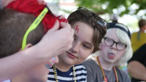 youth sit under a tree visiting after having their faced painted with gay pride colors and flags during spencer pride, saturday, june 3, 2017 in... - teenagers only stock videos & royalty-free footage