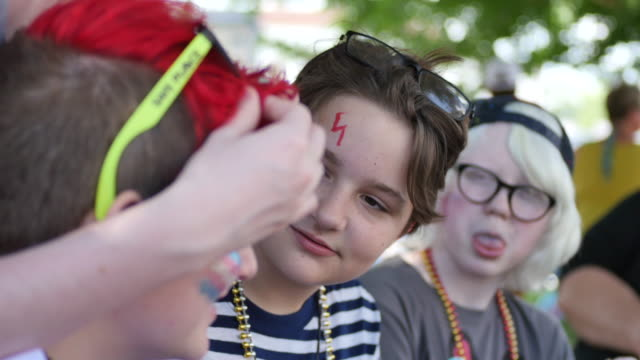 youth sit under a tree visiting after having their faced painted with gay pride colors and flags during spencer pride, saturday, june 3, 2017 in... - nur teenager stock-videos und b-roll-filmmaterial