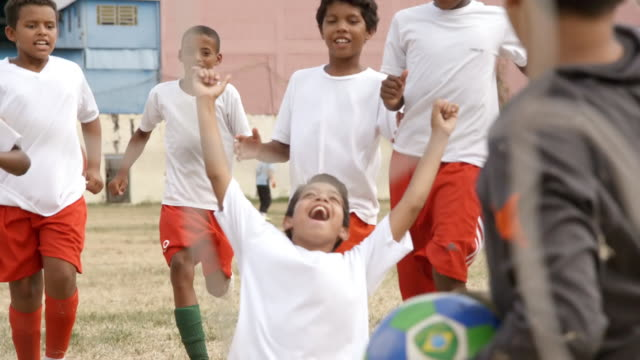 youth soccer team rushes to hug player and celebrate winning goal - goal stock videos & royalty-free footage