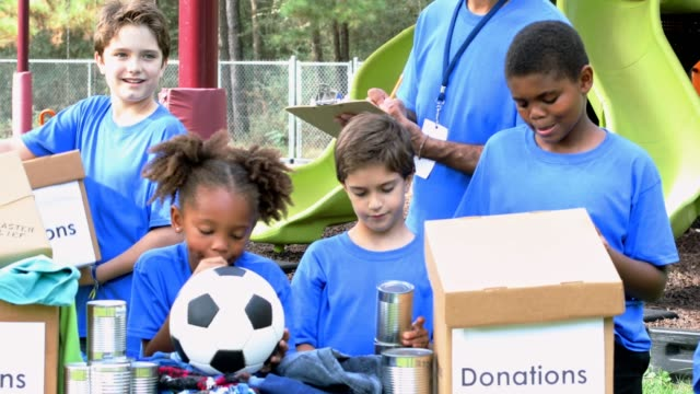 youth sports team collects items for disaster relief - charity benefit stock videos & royalty-free footage