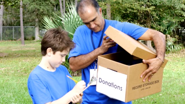 youth sports team collects items for disaster relief - charitable donation stock videos & royalty-free footage