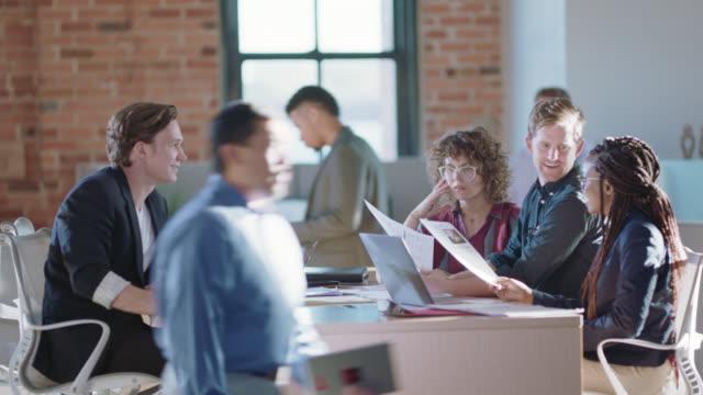 vídeos y material grabado en eventos de stock de youthful group of business colleagues discuss new ideas together while in a busy office - motivación
