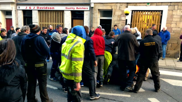 youths chase after the leather ball during the annual 'fastern eve handba' event in jedburgh's high street in the scottish borders on february 22,... - ジェドバラ点の映像素材/bロール