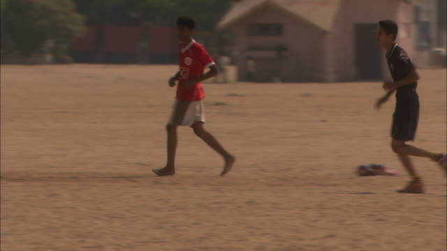 Youths play football on sandy beach team scores Available in HD.
