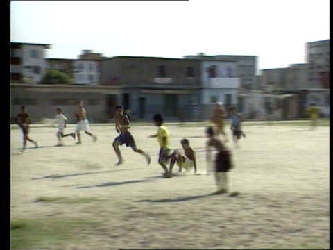 youths playing football on dusty pitch shanty town people on street in shanty town children playing football children practising goal celebrations cf... - fifa stock videos & royalty-free footage