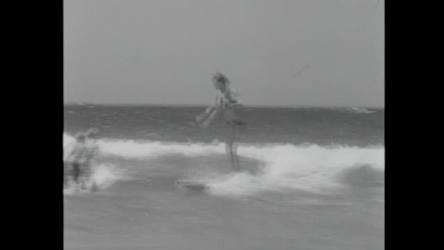 youths wearing board shorts surfing on longboards in whitewash, including teenage girl wearing bikini and surfing / close up legs of boy running into... - running shorts stock videos & royalty-free footage