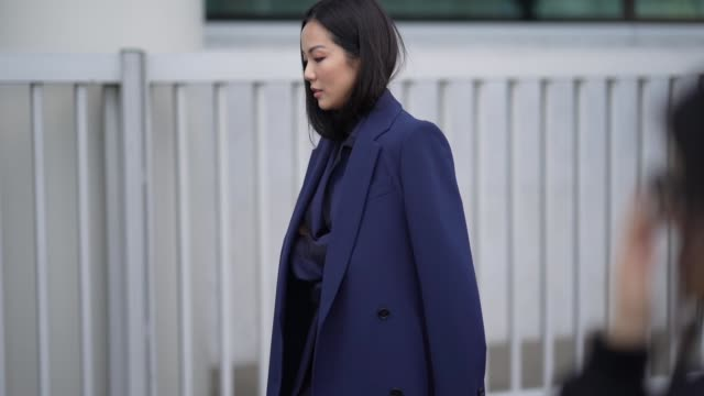 yoyo cao wears a blue long coat, a blue and black striped jacket, flared suit pants, black pointy shoes, outside boss, during milan fashion week... - black colour stock videos & royalty-free footage