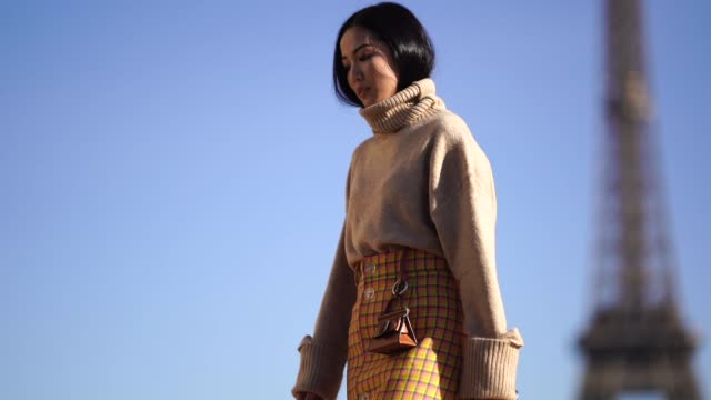 Yoyo Cao wears a brown pullover with turtleneck a yellow checked skirt outside Rochas during Paris Fashion Week Womenswear Spring/Summer 2019 on...