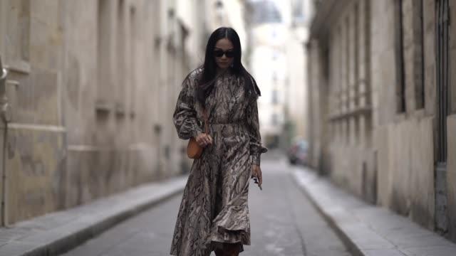vídeos y material grabado en eventos de stock de yoyo cao wears a snake print dress, a brown bag, brown leather boots, sunglasses, outside thom browne, during paris fashion week womenswear... - vestimenta para mujer
