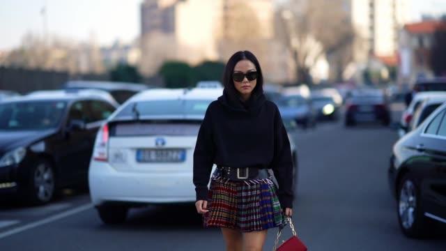 yoyo cao wears sunglasses a black hooded sweatshirt a black belt a colorful pleated mini skirt a red bag black prada midcalf laceup platform boots... - sweatshirt stock videos & royalty-free footage