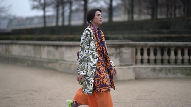 Yu Masui wears a floral print white coat a floral print orange and blue jacket outside Kenzo during Paris Fashion Week Menswear F/W 20192020 on...
