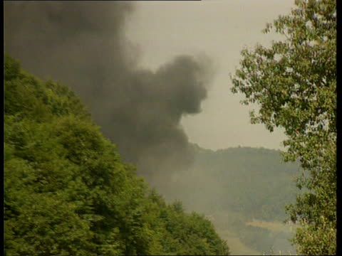 stockvideo's en b-roll-footage met yugoslavian civil war itn ms pall of black smoke seen amongst trees pull out - joegoslavië