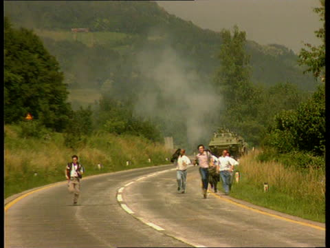 vidéos et rushes de yugoslavian civil war itn ms press running down road towards g/a soko jastreb dropping down and then flying low over trees as firing - slovénie