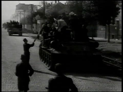stockvideo's en b-roll-footage met yugoslavian soldiers riding tank man w/ yugoslavia flag ws partisan soldiers hanging flag on wire pole wwii nazi germany - joegoslavië