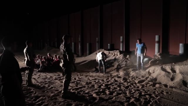 yuma border patrol agents apprehend a large group of illegal immigrants clearing sand and making entry under an older section of border wall near san... - 密輸点の映像素材/bロール