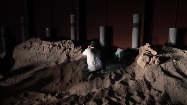 yuma border patrol agents apprehend a large group of illegal immigrants clearing sand and making entry under an older section of border wall near san... - forbidden stock videos & royalty-free footage