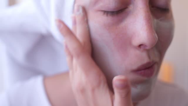 vídeos y material grabado en eventos de stock de yung mujer poniendo la máscara facial en el rostro - limpiador facial