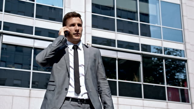 slo mo yuppie have a call while leaving the office - yuppie stock videos and b-roll footage