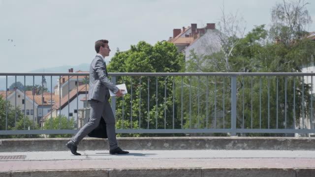 Yuppie walking across the bridge in city